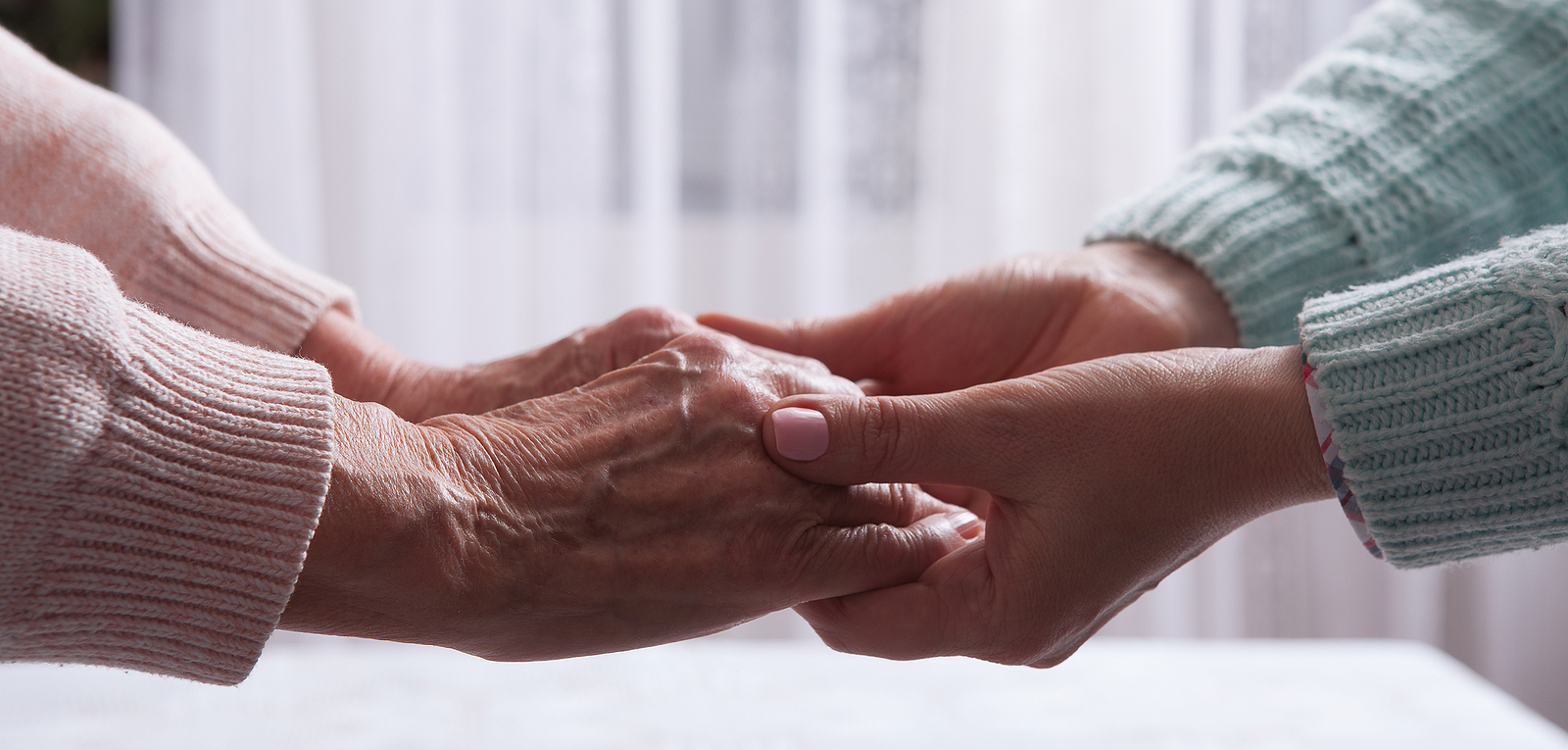 Closeup of elderly woman holding hands of caregiver.